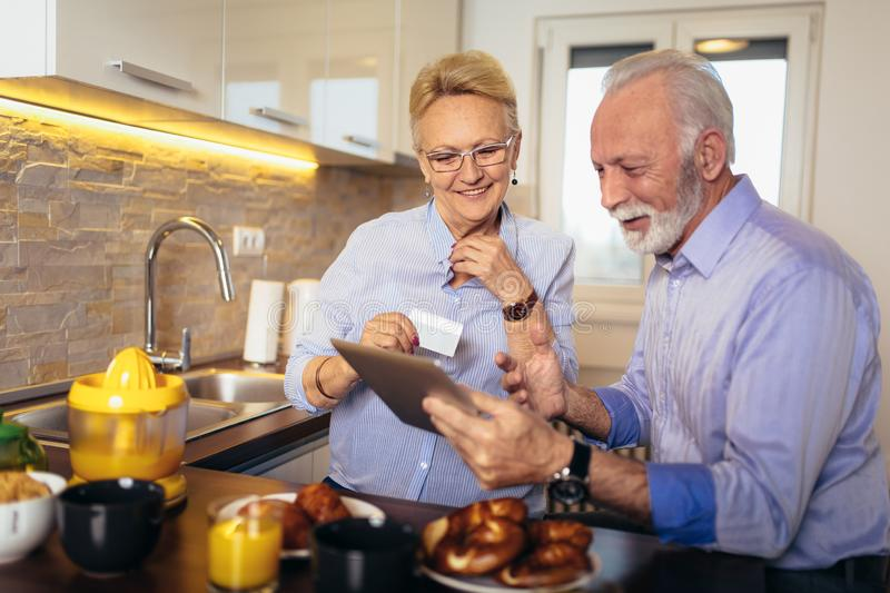 Senior couple shopping online with tablet and credit card. Modern senior couple shopping online with tablet and credit card royalty free stock image