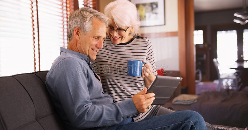 Modern senior couple sitting on couch with tablet royalty free stock image