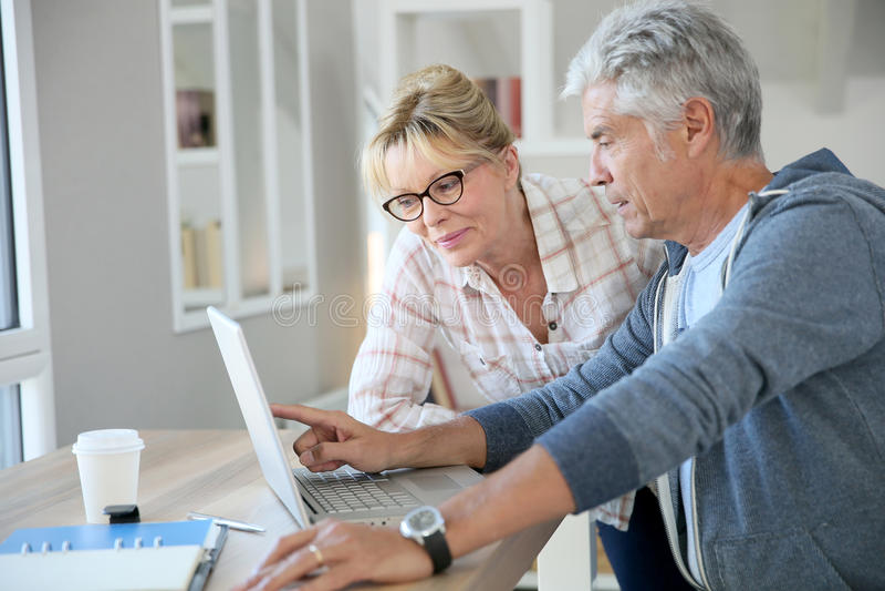 Modern senior couple using laptop royalty free stock photography