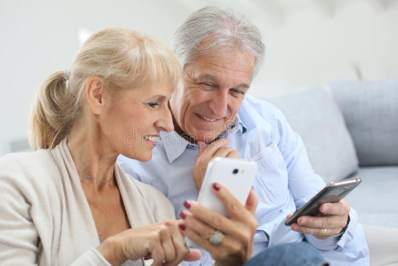 Modern senior couple using smartphones stock image