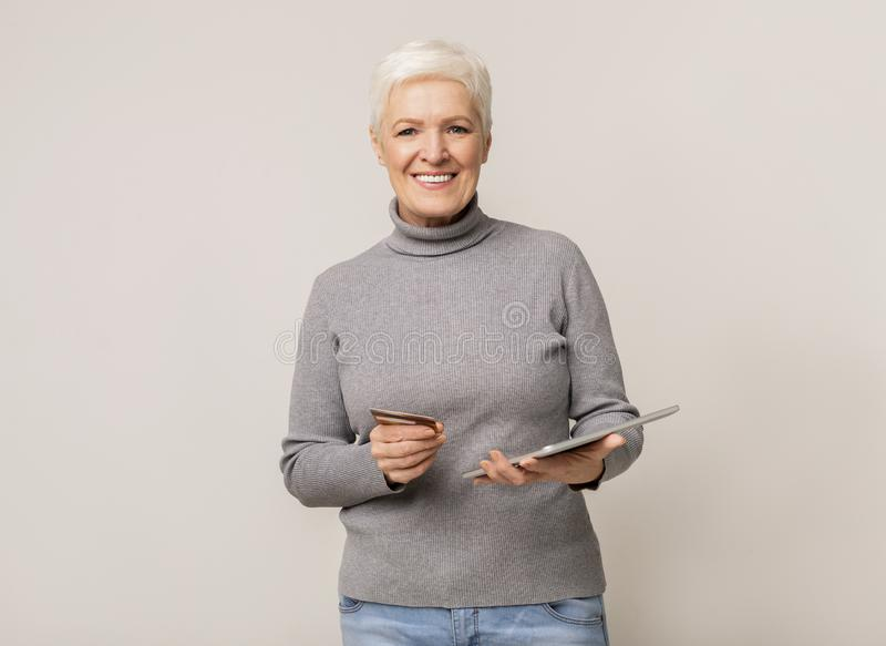 Modern senior woman shopping online with tablet and credit card stock photography