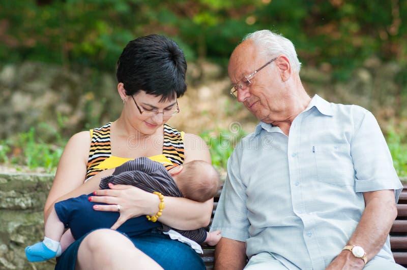 Modern ser ungen som suger ett bröst arkivfoto