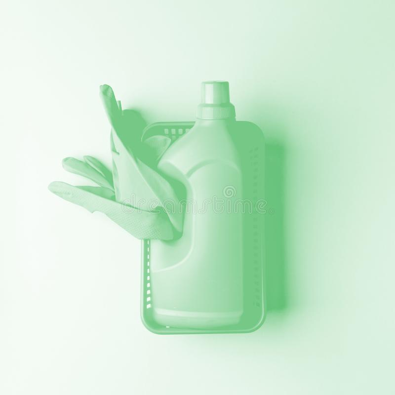 Modern set of professional cleaning service on trendy neo mint pastel back. Group of hygiene housekeeping. Rubber gloves, bottle. And sponge cleaner. Monochrome stock photography