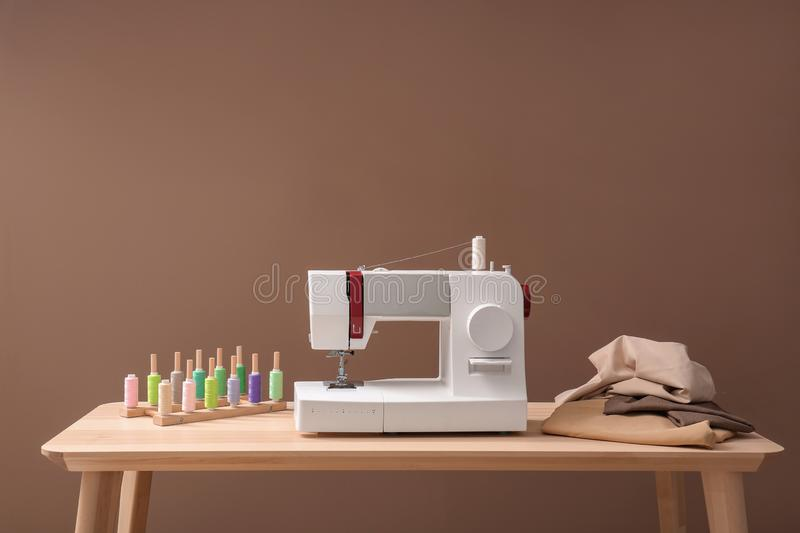 Modern sewing machine, set of threads and fabric on table against color background royalty free stock photo