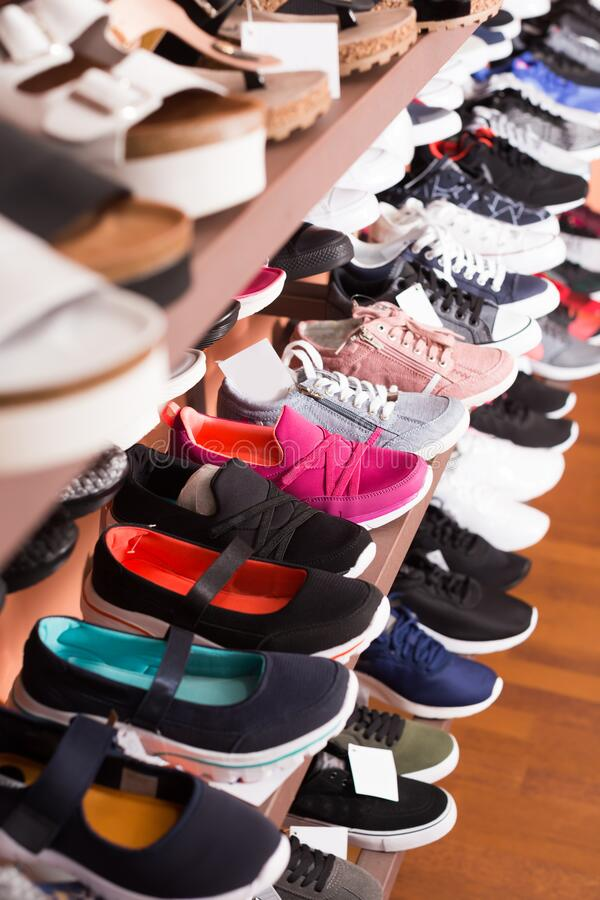 Modern shoes are standing on shelves. In shoes store stock images
