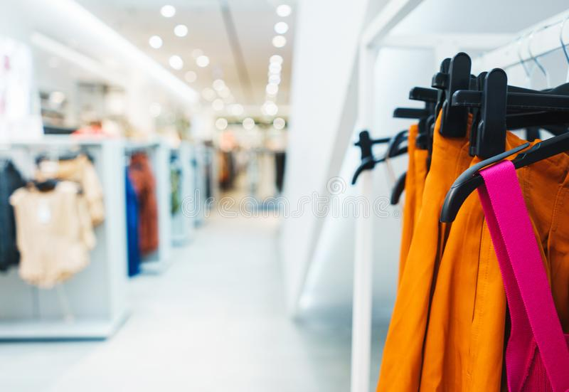 Hangers bright fashionable clothes. T-shirts, blouses and shirts on a hanger in the mall close-up. Modern show room selling clothes men, women and children stock photo