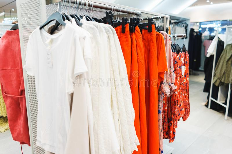 Hangers bright fashionable clothes. T-shirts, blouses and shirts on a hanger in the mall close-up. Modern show room selling clothes men, women and children stock image