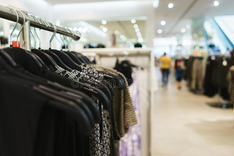 Hangers bright fashionable clothes. T-shirts, blouses and shirts on a hanger in the mall close-up. Modern show room selling clothes men, women and children royalty free stock image