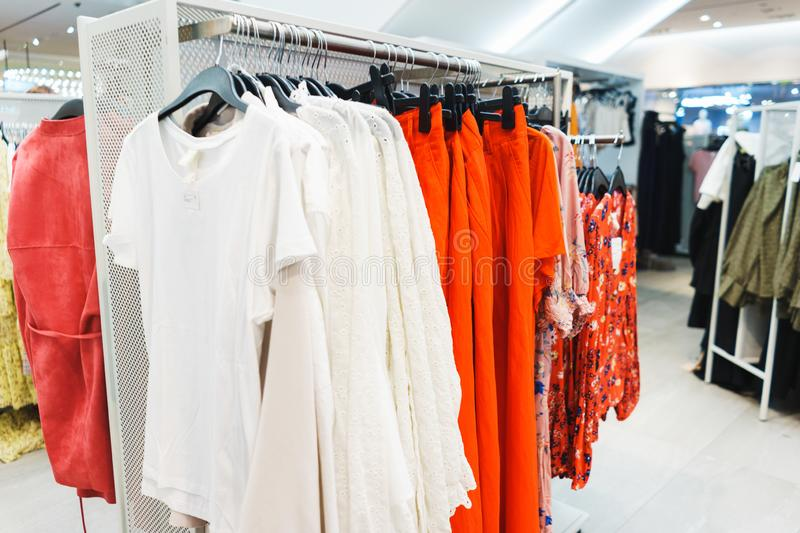 Hangers bright fashionable clothes. T-shirts, blouses and shirts on a hanger in the mall close-up. Modern show room selling clothes men, women and children royalty free stock images