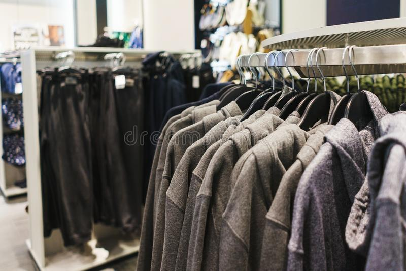 Hangers bright fashionable clothes. T-shirts, blouses and shirts on a hanger in the mall close-up. Modern show room selling clothes men, women and children royalty free stock photo