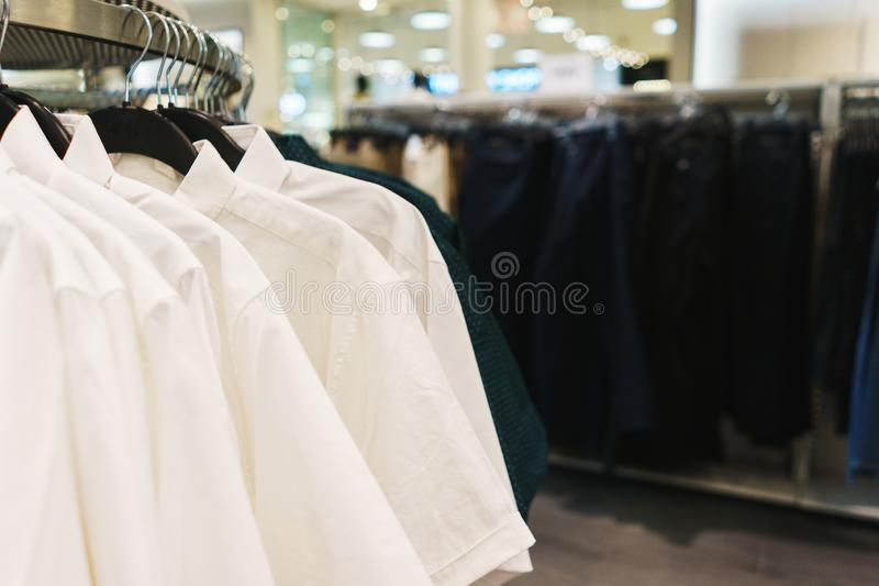 Hangers bright fashionable clothes. T-shirts, blouses and shirts on a hanger in the mall close-up. Modern show room selling clothes men, women and children royalty free stock photography