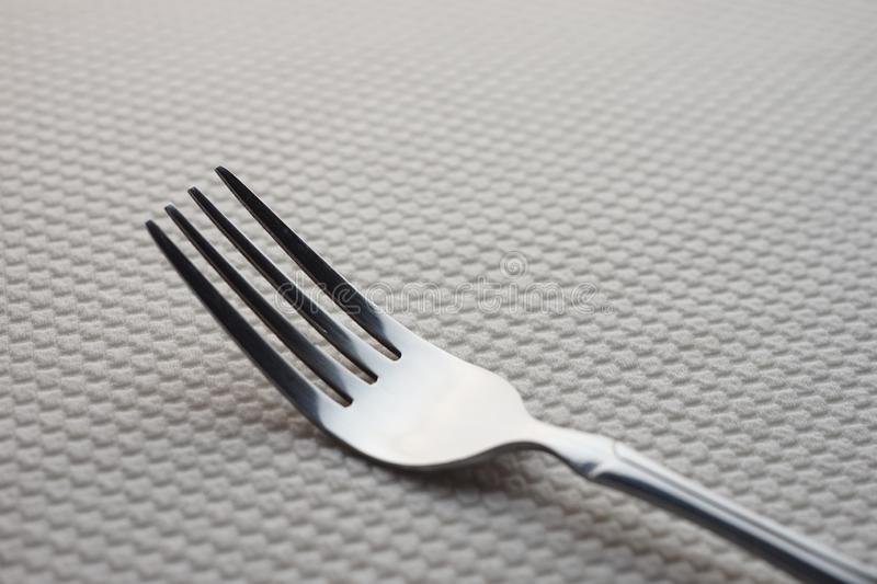 Modern silver stainless steel fork on a table with a white tablecloth.  stock photos