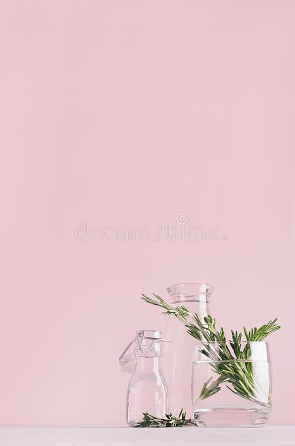 Modern simple art pink home decor with green plant in transparent vases on soft light white wood table, vertical. royalty free stock photo