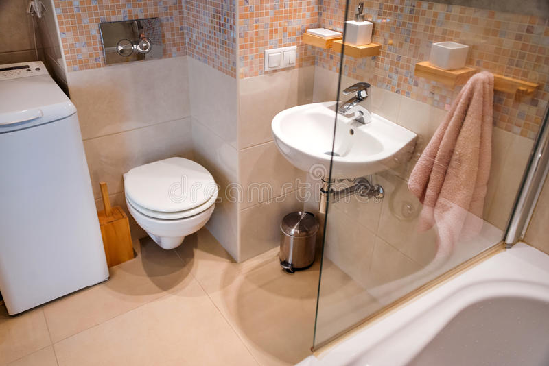 Modern simple interior in light apartments. Bathroom interior with glass door shower and mirror. stock photography