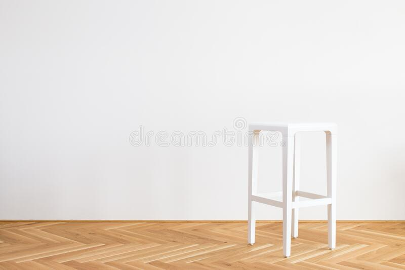 Modern simplistic white chair on a wooden floor in front of white background. Nice modern simplistic white chair on a wooden floor in front of white background royalty free stock photography