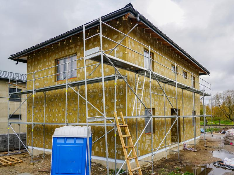 Modern single family two store home under construction, enclosed with scaffolds, thermal insulation royalty free stock photos