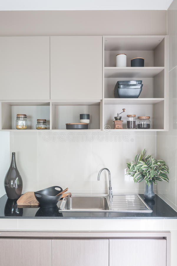 Modern sink on black kitchen counter stock image