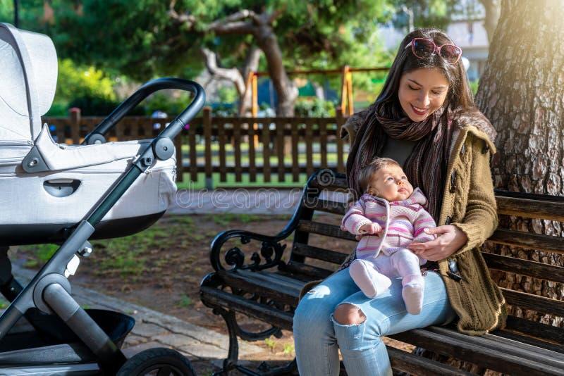 Modern sitter med hennes nyfött behandla som ett barn flickan på en bänk i parkerar royaltyfria bilder