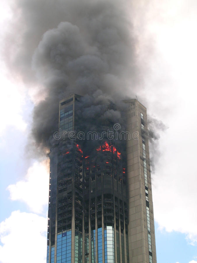 Modern skyscraper building on fire stock images