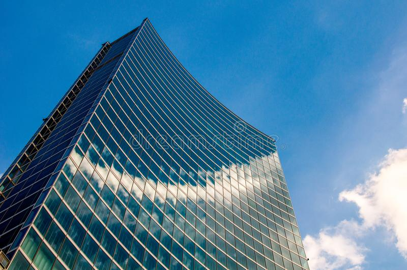 Modern skyscraper with reflections of clouds on windows royalty free stock photo