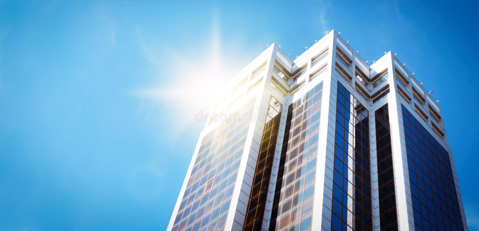 Skyscraper with tinted windows against blue sky, low angle view. Building corporation. Modern skyscraper with tinted windows against blue sky, low angle view royalty free stock photo