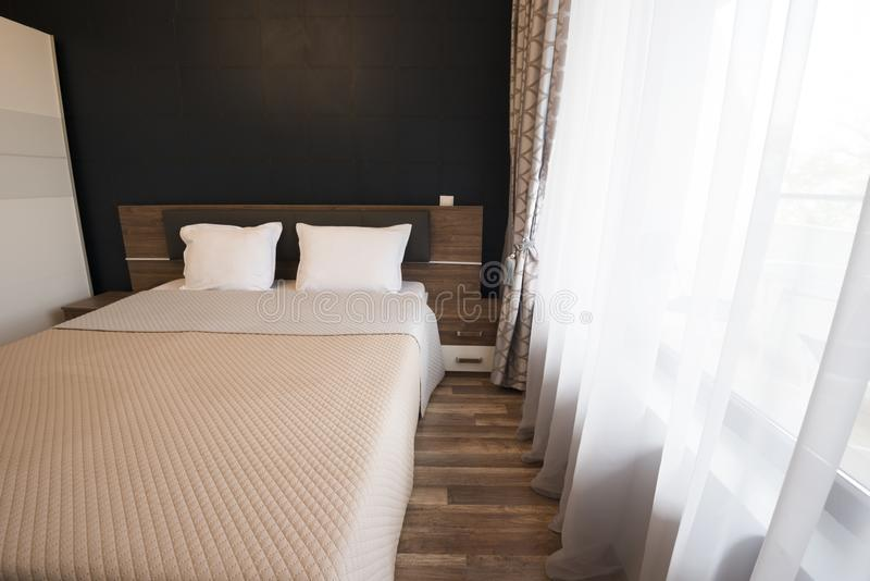 Modern slaapkamer binnenlands ontwerp De ruimte van het luxebed met bruine kleurentoon De vensters met lange gordijnen en wijkt a royalty-vrije stock afbeelding
