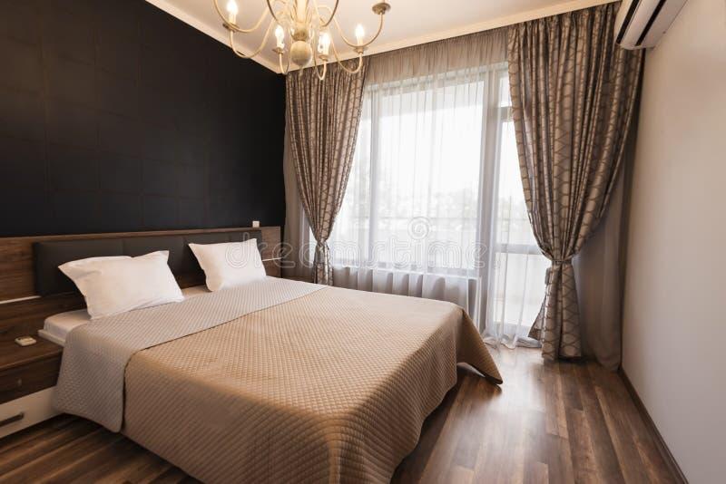 Modern slaapkamer binnenlands ontwerp De ruimte van het luxebed met bruine kleurentoon De vensters met lange gordijnen en wijkt a stock fotografie