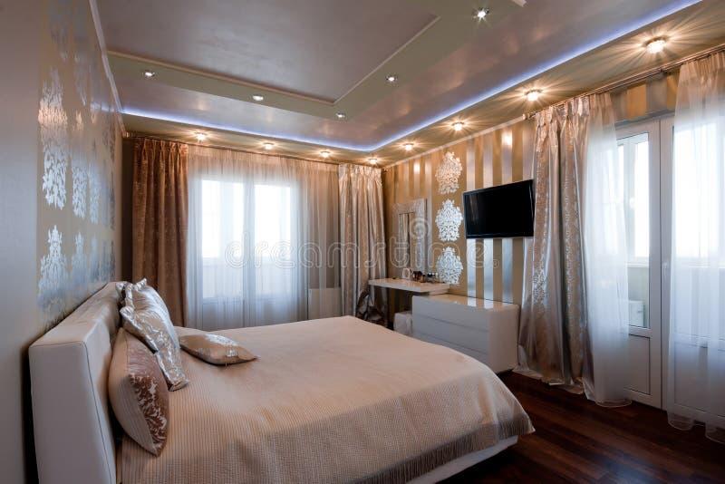 Modern slaapkamerbinnenland in gouden kleuren stock afbeelding