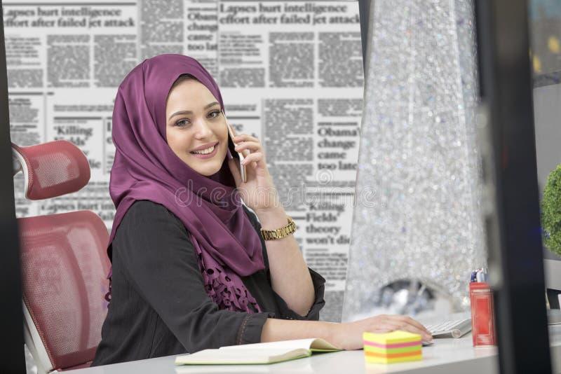 Modern smart kvinnlig islamisk kontorsarbetare som talar på telefonen fotografering för bildbyråer