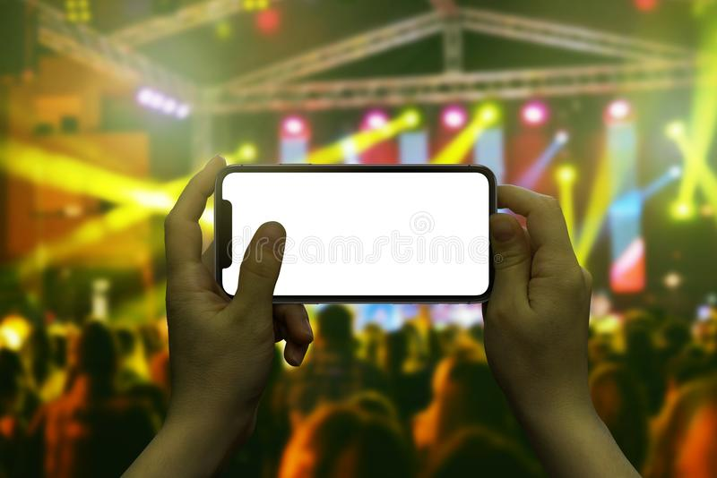 Modern smart phone in woman hand. Live music concert in background stock photo