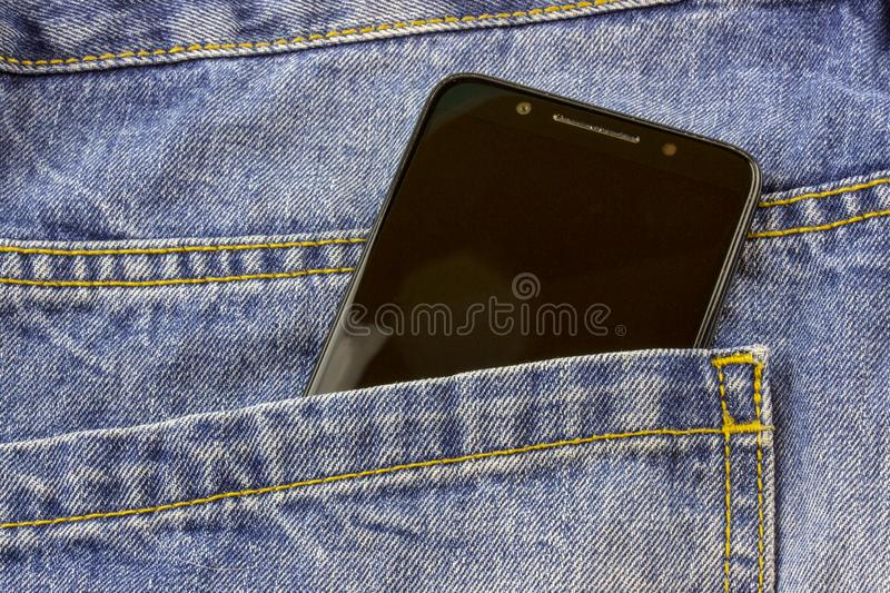 Modern smartphone in the pocket of jeans, close-up, Cell phone in the pocket of jeans in blue jeans royalty free stock photo
