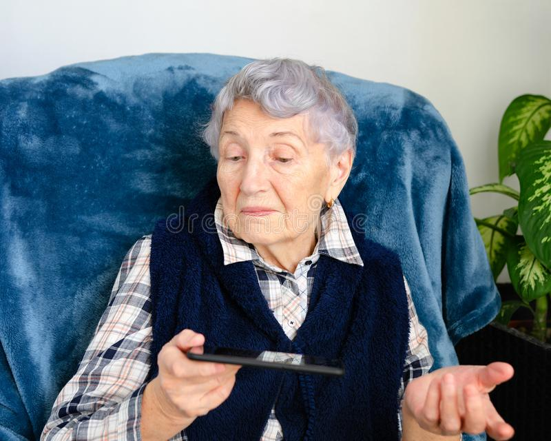 Modern smartphone results the elderly woman in bewilderment royalty free stock images