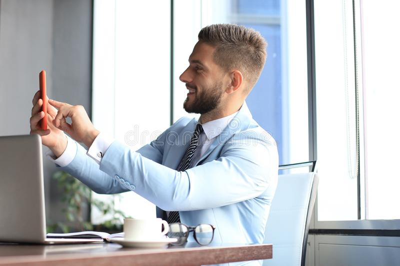 Modern smiling businessman is taking a selfie in the office royalty free stock image