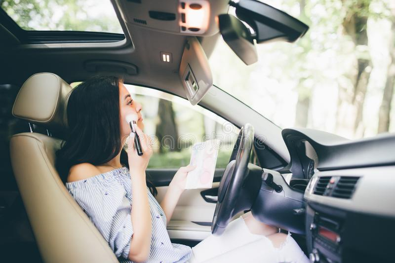 Modern smiling girl in car talk on phone and make-up on mirror royalty free stock photo