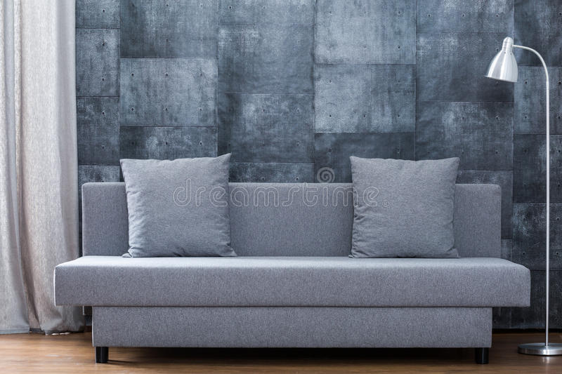 Modern sofa and concrete wallpaper. Picture of modern sofa and concrete wallpaper in lounge stock images