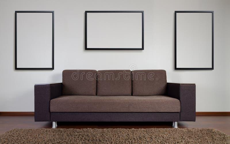 Modern soffa med vägggarneringramar royaltyfri fotografi