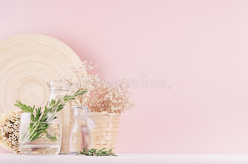 Modern soft light pink pastel home interior with green plant, dried white flowers, beige bamboo plate on white wood background. royalty free stock photos