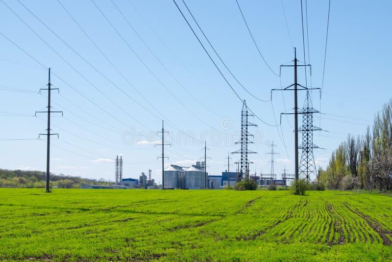 Modern sojabönabearbetningsanläggning, jordbruks- silor mot grönt fält och blå himmel Lagring och uttorkning av korn, vete, havre arkivfoton