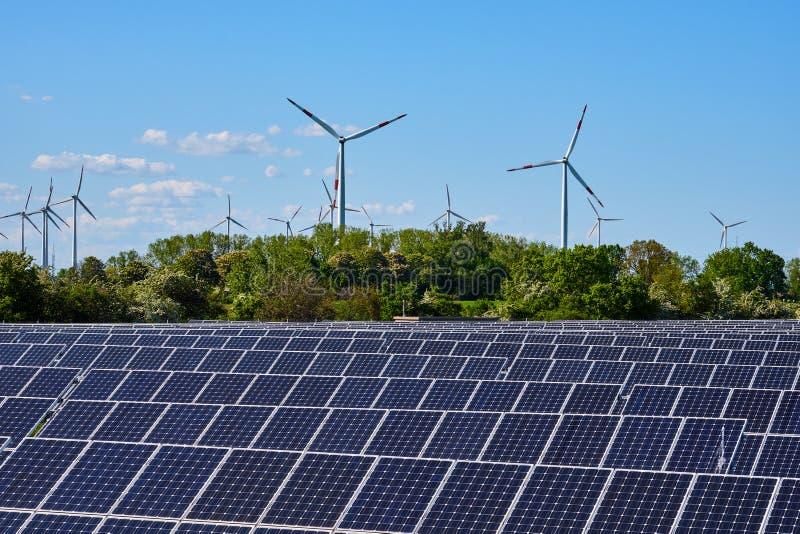Modern solar power plant with wind turbines stock photo