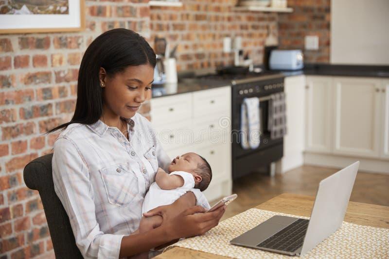 Modern som arbetar på bärbara datorn, rymmer den nyfödda sonen och överför text arkivbild