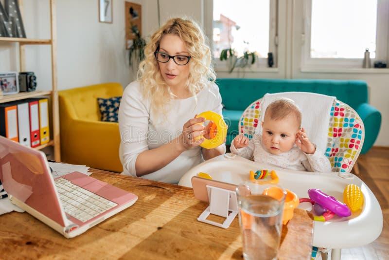 Modern som arbetar på hemmastatt kontor för bärbar dator med henne, behandla som ett barn royaltyfria foton