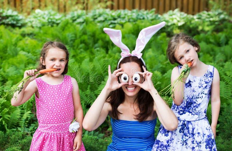 Modern som bär Bunny Ears och enfaldiga ögon, poserar med barn royaltyfri bild