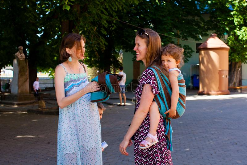 Modern som bär henne, behandla som ett barn möta en vän arkivbilder