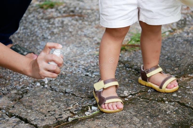 Modern som besprutar kryp- eller myggaimpregneringsmedel på hudflickan, myggaimpregneringsmedlet för, behandla som ett barn, små  royaltyfri fotografi