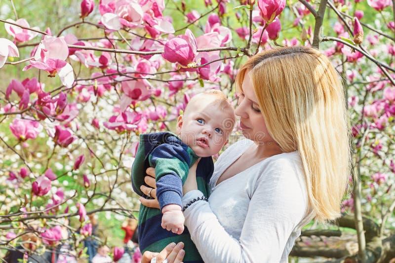 Modern som går med henne, behandla som ett barn sonen i trädgården av blommande magnolior royaltyfria bilder