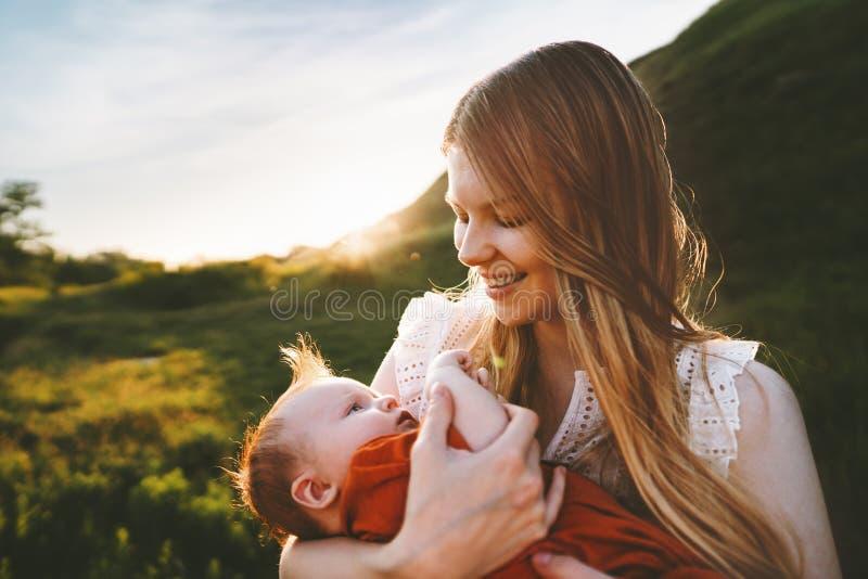 Modern som g?r med sp?dbarnet, behandla som ett barn den utomhus- lyckliga familjen arkivbild