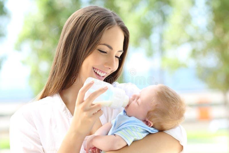 Modern som ger att mata med flaska till henne, behandla som ett barn arkivfoto