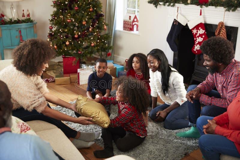 Modern som ger dottergåvan som den mång- utvecklingsfamiljen, firar jul hemma tillsammans royaltyfri fotografi