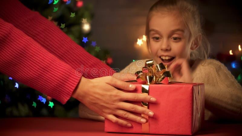 Modern som ger julgåvan till den upphetsade dottern, semestrar hemsändning royaltyfri fotografi