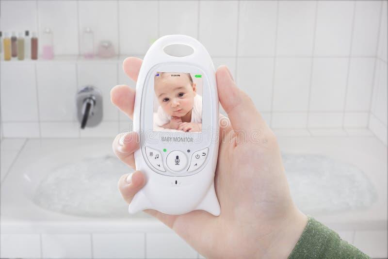 Modern som kontrollerar hans nyfött till och med, behandla som ett barn bildskärmen arkivfoton
